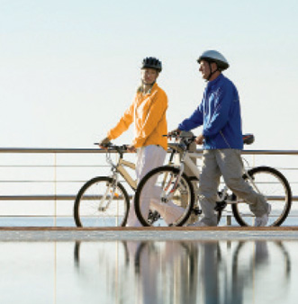 Image: man and woman walking bikes on bridge by water with helmets. Woman has yellow jacket and white pants. Man has blue jacket and beige pants