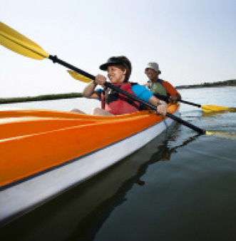 Image: man and woman in orange an white kayak with hats on and yellow oars. Woman has black hat and red life jactet.  Man has white hat and green lifejacket